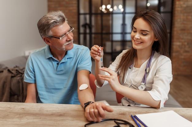 De vrouwelijke arts vaccineert thuis bij de oude patiënt
