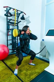 De vrouwelijke atleet die zij uitoefenen uitoefenen in een ems-geschiktheidsstudio