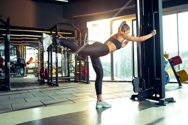 De vrouwelijke atleet traint hard in de sportschool fitness en gezond leven concept