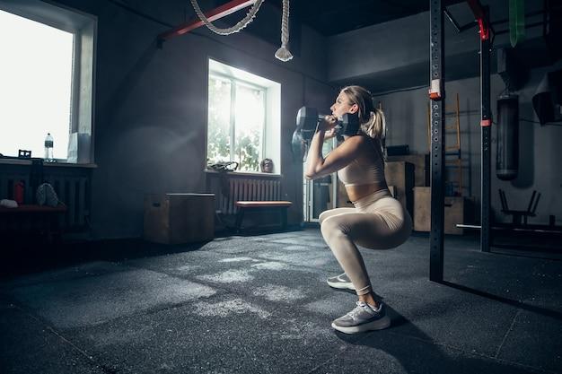 De vrouwelijke atleet traint hard in de sportschool. fitness en gezond leven concept.
