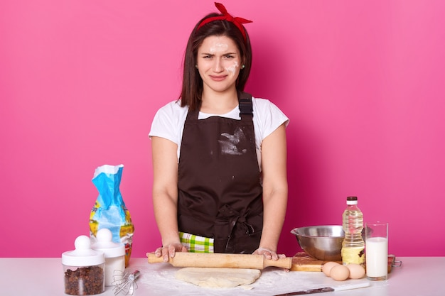 De vrouwelijke bakker bevindt zich op werkplaats bij de bakselvervaardiging. jonge kok draagt bruine schort en casual wit t-shirt, glimlacht, heeft prettige gezichtsuitdrukkingen. bakary en culinair concept.