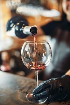 De vrouwelijke barman dient handschoenen in en giet wijn