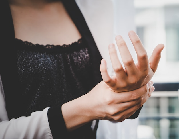De vrouwelijke beambte heeft de wond van het bureausyndroom op haar pols