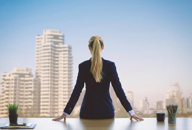 De vrouwelijke bedrijfsvrouw kijkt uit de vensters voor succes