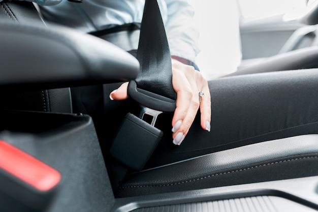 De vrouwelijke bestuurder maakt veiligheidsgordelclose-up vast