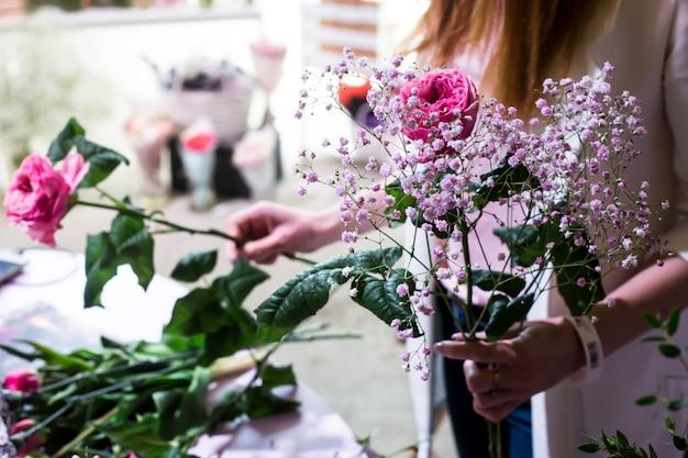 De vrouwelijke bloemist creëert een zacht boeket van gypsophila en rozen