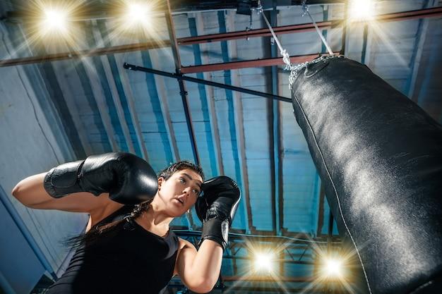 De vrouwelijke bokser en afro-amerikaanse mannelijke bokser trainingsbox in de sportschool