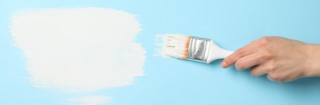 De vrouwelijke borstel van de handholding op blauwe oppervlakte met witte verfslagen