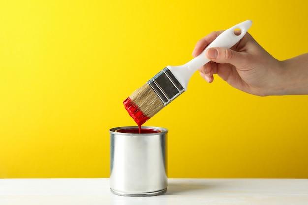 De vrouwelijke borstel van de handholding over het blik met rode verf tegen gele oppervlakte
