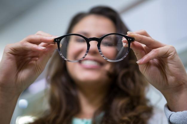 De vrouwelijke bril van de klantenholding in optische opslag