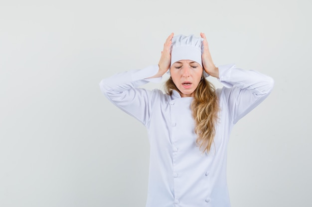 De vrouwelijke chef-kok die hoofd in handen in wit uniform vastklemt en moe kijkt.