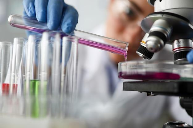 De vrouwelijke chemicus houdt reageerbuis glas in hand close-up