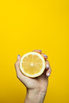 De vrouwelijke citroen van de handgreep op gele muur