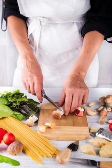 De vrouwelijke gesneden handen bereiden ingrediënten voor deegwaren met paddestoelen voor