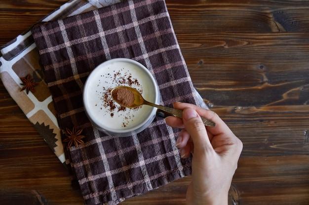 De vrouwelijke hand bestrooit cappuccino met kaneel copyspace