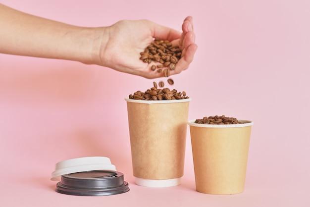 De vrouwelijke hand bestrooit koffiebonen in koffiedocument kop op roze achtergrond