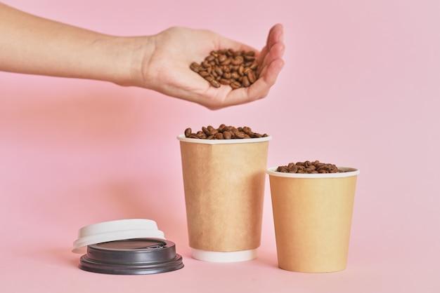 De vrouwelijke hand bestrooit koffiebonen in koffiedocument kop