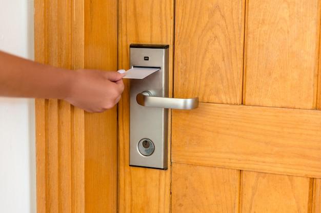 De vrouwelijke hand die en magnetische sleutelkaart zet zet binnen om hoteldeur te openen