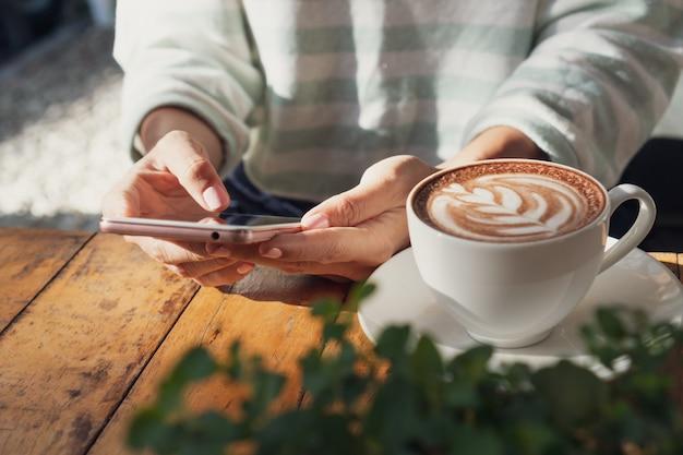 De vrouwelijke hand die mobiele telefoon met een kop van hete cacao of chocolade op houten lijst met behulp van, sluit omhoog