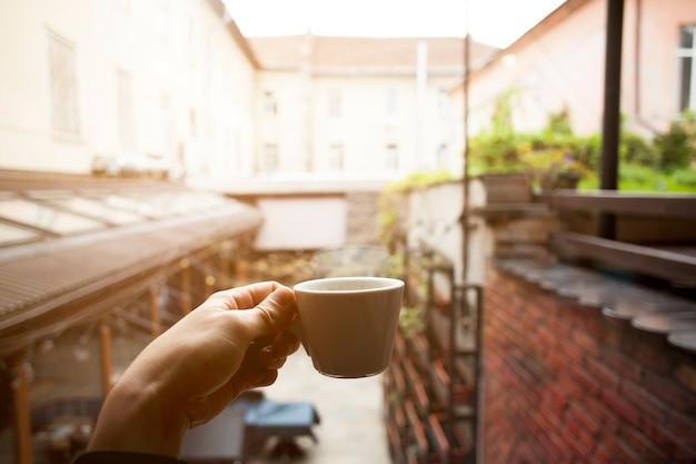 De vrouwelijke hand die van de close-up hete koffiekop houdt