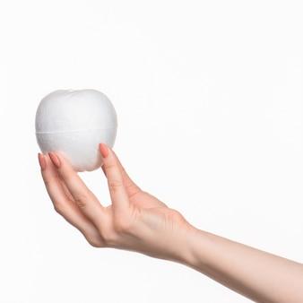 De vrouwelijke hand die wit leeg piepschuimovaal houdt tegen de witte achtergrond met juiste schaduw