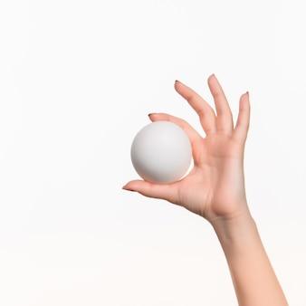 De vrouwelijke hand die witte lege piepschuimbal houdt tegen het wit.