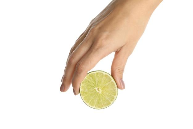 De vrouwelijke hand houdt de helft van limoen vast, geïsoleerd op een witte achtergrond