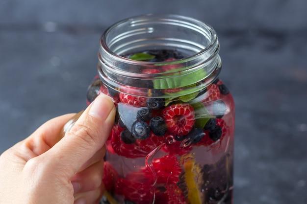 De vrouwelijke hand houdt de mok van de metselaarkruik met verse koele detoxdrank met frambozen, bosbessen. limonade in een glas met een munt. het concept van goede voeding en gezond eten. fitness dieet. detailopname
