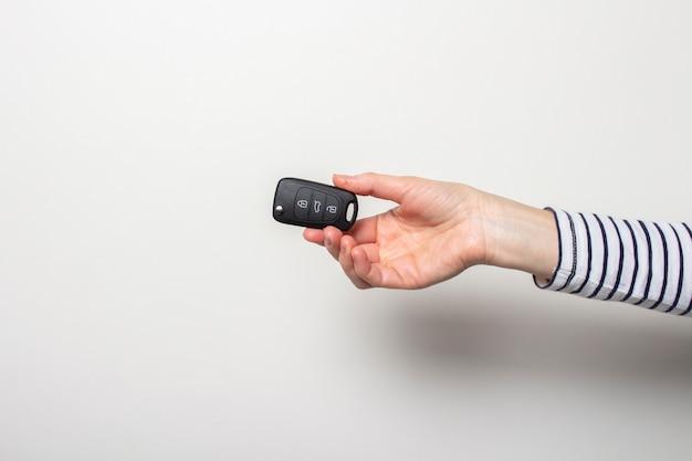 De vrouwelijke hand houdt een autosleutel op een wit