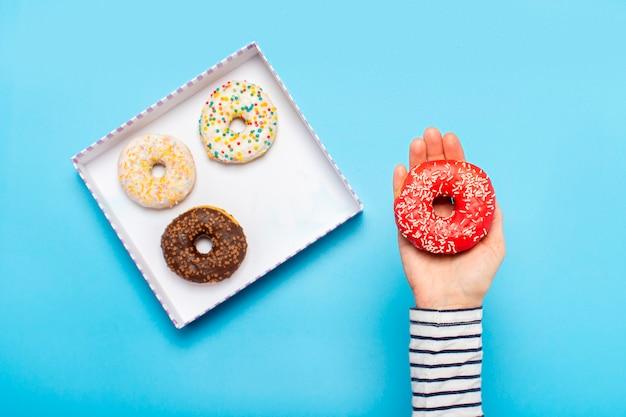 De vrouwelijke hand houdt een doughnut op een blauw. concept zoetwarenwinkel, gebak, koffieshop.