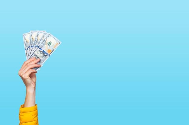 De vrouwelijke hand houdt geld, dollarbankbiljetten op een blauwe achtergrond