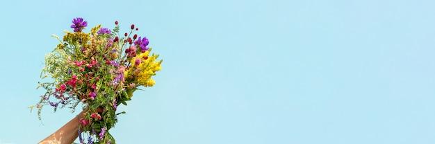 De vrouwelijke hand houdt helder kleurrijk boeket van wilde bloemen tegen blauwe hemel.