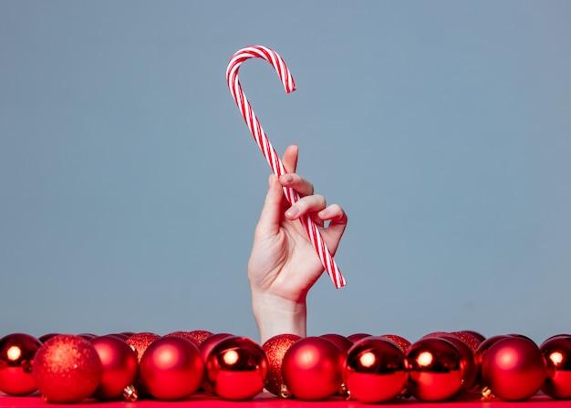 De vrouwelijke hand houdt het riet van het kerstmissuikergoed op grijze achtergrond met rond snuisterijen
