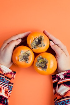 De vrouwelijke hand houdt rijpe dadelpruim drie op sinaasappel.