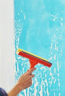 De vrouwelijke hand maakt het raam schoon met een schuimrubberen borstel