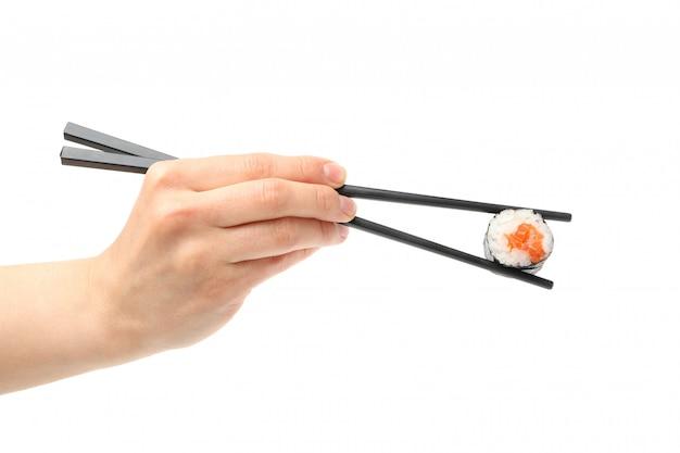 De vrouwelijke hand met eetstokjes houdt sushibroodje, dat op witte oppervlakte wordt geïsoleerd