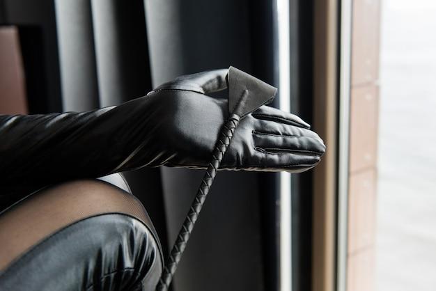 De vrouwelijke hand met gewas ranselt close-up