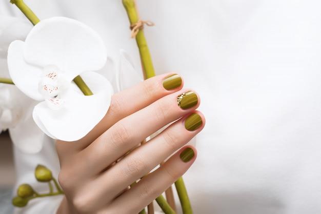 De vrouwelijke hand met groen spijkerontwerp, sluit omhoog.