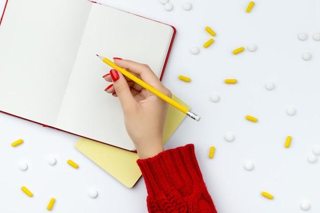 De vrouwelijke hand schrijft in een blocnote met pillen die op de achtergrond worden verspreid
