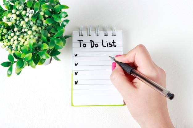 De vrouwelijke hand schrijft om lijst in notitieboekje te doen