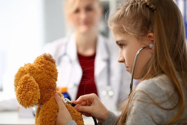 De vrouwelijke hand van de stethoscoop van de meisjegreep luistert
