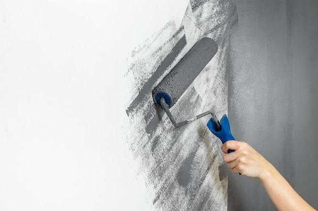 De vrouwelijke handclose-up schildert een muur in grijs. het concept van reparatie, verandering, ontwerp