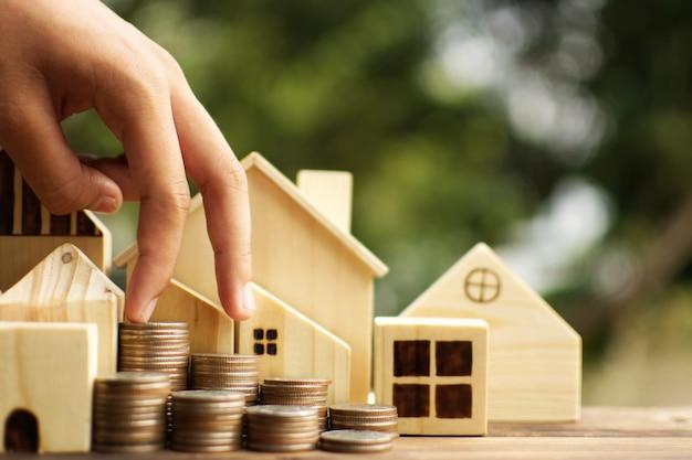 De vrouwelijke handen beschermen het kleine houten huismodel op plank en boom bokeh achtergrond.