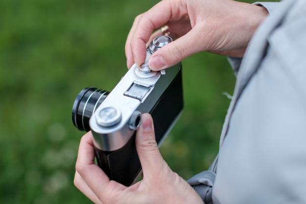 De vrouwelijke handen die retro fotocamera houden en passen blootstelling op achtergrondgras aan.