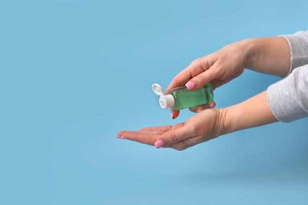 De vrouwelijke handen drukken het gel van het handdesinfecterende middel van fles op blauw