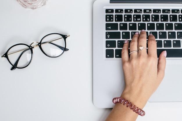 De vrouwelijke handen gebruiken laptop toetsenbord op witte lijst