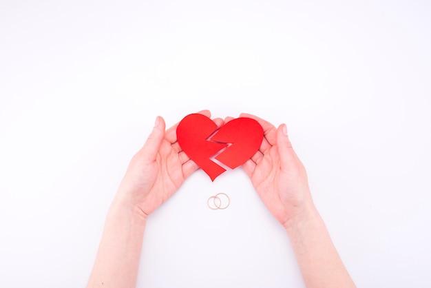 De vrouwelijke handen houden een gebroken hart op een wit