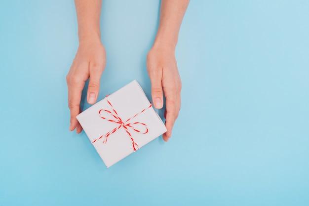 De vrouwelijke handen houden een witte giftdoos met een dun lint als cadeau voor kerstmis, nieuwjaar, moederdag of verjaardag op een blauwe tafel achtergrond, bovenaanzicht. plaats voor tekst.