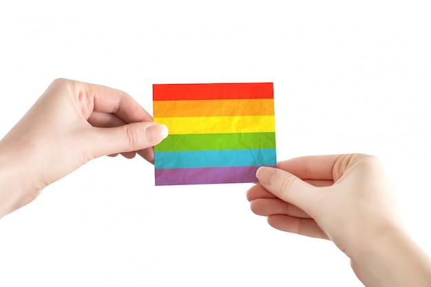 De vrouwelijke handen houden lgbt-vlagdocument dat op een witte achtergrond, symboliek, gemeenschap wordt geïsoleerd. lgbt-concept, trotsdag. vrijheid en rechten van minderheden