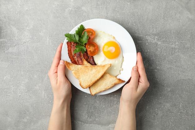 De vrouwelijke handen houden plaat met gebraden eieren op grijze oppervlakte, hoogste mening